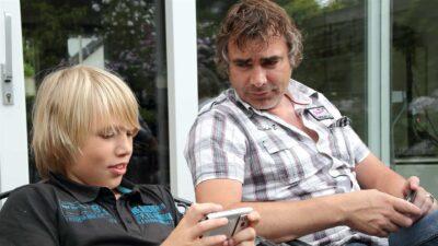 Man zit naast jongetje die kijkt op zijn mobiel