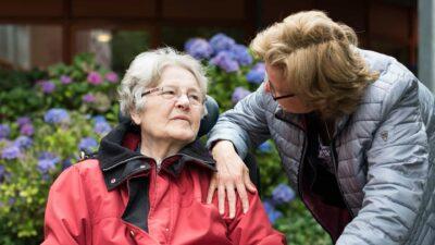 Vrouw praat met oudere vrouw in rolstoel