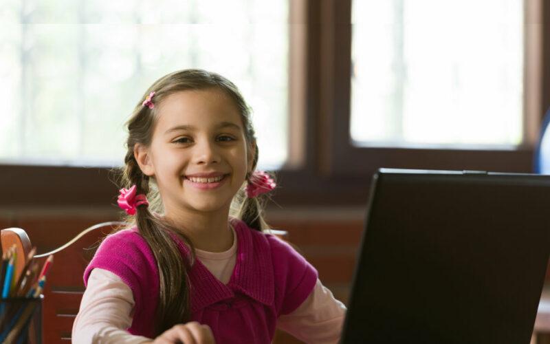 Meisje met laptop maakt huiswerk